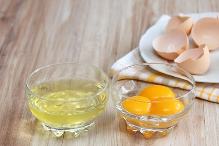egg white: How to separate egg- white and yolks into two bowls and egg shells  are at background