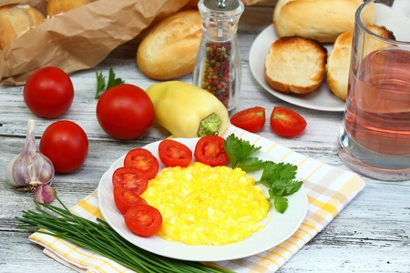 baguet: Delicious breakfast of scrambled eggs, baguettes  and vegetable on the plate