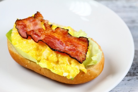 baguet: Delicious sandwich with bacon, scrambled egg and lettuce served on a plate