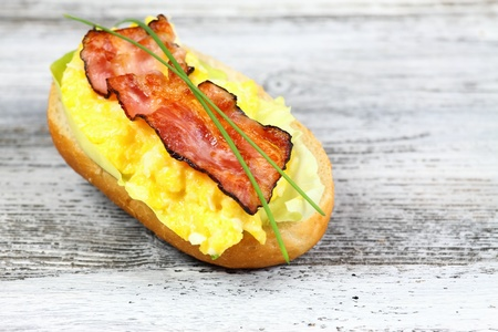 baguet: Delicious sandwich with bacon, scrambled egg and lettuce decorated with chives on a wooden table.