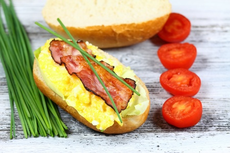 baguet: Delicious sandwich with bacon, scrambled egg and lettuce decorated with chives and tomatoes on a wooden table.