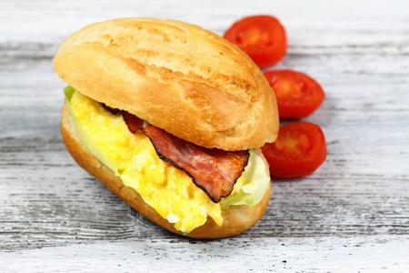 baguet: Delicious sandwich with bacon, scrambled egg and lettuce decorated with tomatoes on a wooden table. Stock Photo