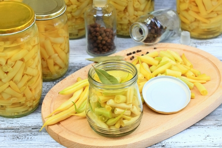 bay leaf: Homemade preserved yellow beans in spicy  pickle, cut beans with bay leaf in the jar at the front