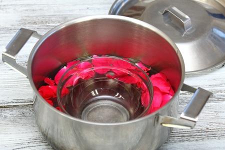 destilacion: la producción casera de agua de rosas en una forma de destilación casera de pétalos de rosa, una tapa se gira al revés en el bote