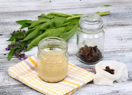 Alternative medicine,  filtering Comfrey ointment good for bones,  fresh comfrey and dried comfrey roots around
