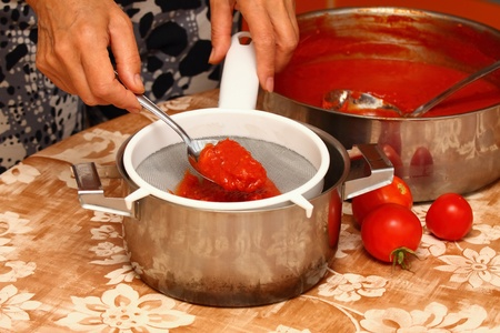 Woman making ketchup, tomatoes boiled to mush pressed through the strainer Stock Photo