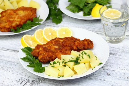 wiener: Wiener schnitzel and boiled potatoes  with  chopped chives, sliced lemon and lettuce
