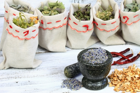 milfoil: Mortar with lavender herb, dried herbs and mushrooms;  sages, pepper mint, milfoil and linden flowers in bags