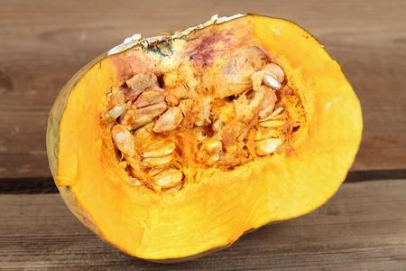 Cut in half rotten pumpkin on wooden board