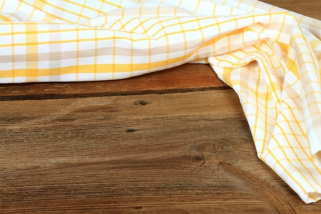 Dish cloth in yellow and white on brown wooden table. Linen tea towel on board, good for background