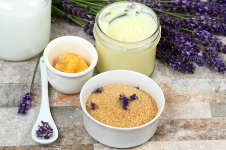 Making  homemade body scrub for clear soft skin.  Made from granulated sugar, bamboo butter, coconut oil and lavender flowers Stock Photo