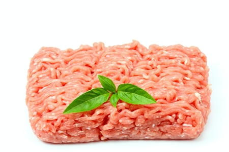 Raw minced pork on the white background, pork meat decorated with basil leaf