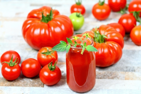 Homemade preserved ketchup from giant beefsteak and common tomatoes in a bottle. Fresh tomatoes are around a bottle, tomato  flower is in a ketchup.