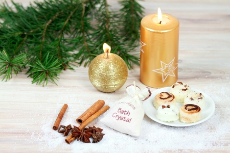 Winter spa concept with candles.  Wellness objects, body cream, bath crystals, cinnamon, nutmeg  on wood table.
