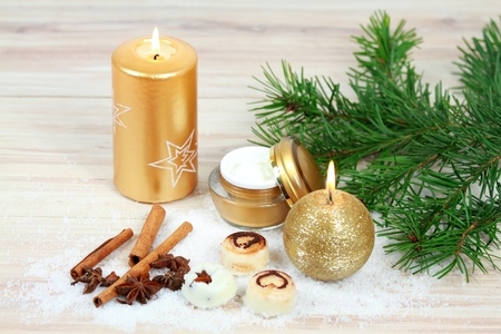 Winter spa concept with candles. Wellness objects, body cream, scrub bars, bath crystals, cinnamon, nutmeg  on wood table.