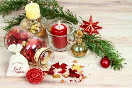 Christmas spa concept with candles and Christmas decoration.  Aromatherapy treatment, aromatic herbs, oil,  bath crystals  on wooden background Stock Photo