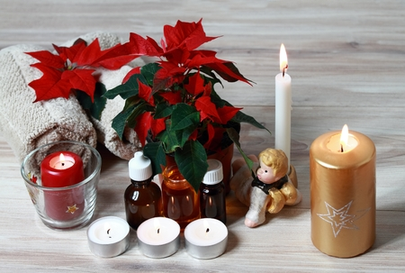 Christmas spa concept with candles and red Christmas flower poinsettia .  Wellness objects,  plant  Euphorbia pulcherrima, towels and essential oil  on the wood table.
