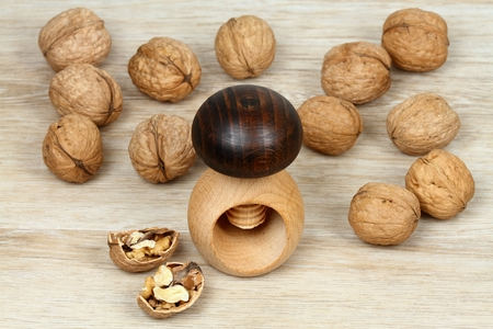 Wooden nutcracker in a shape of mushroom and walnuts. Screw type nut cracker with walnuts on wooden background