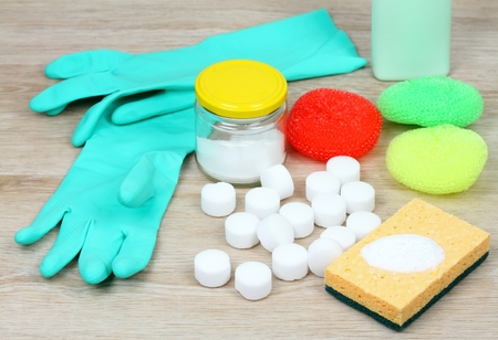 House cleaning products on wooden table. Salt pelets, baking soda (sodium bicarbonate),