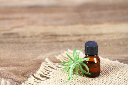 Essential oil, craft bottle, fresh rosemary leaves. Natural beauty care remedy on burlap and brown wooden board