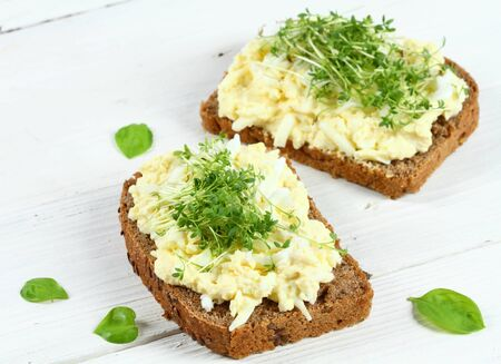 Egg salad over brown bread with garden cress. White background. Homemade spread made from eggs, mayonnaise and mustard.