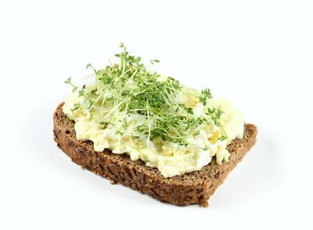 Egg salad over brown bread with garden cress. Homemade spread made from eggs, mayonnaise and mustard on white background Stockfoto