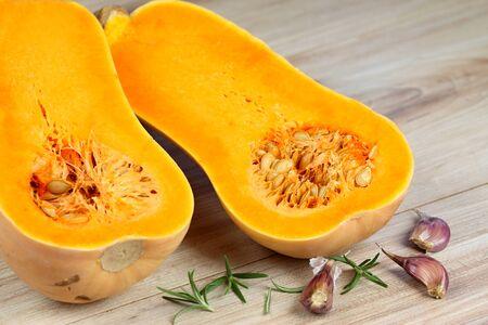 Pumpkin Butternut Liscia cut in half. Yellow delicious pumpkin on wooden table. Stock Photo