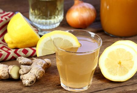 Hot tea against cough and flu made from onion, ginger, lemon and honey. Homemade tea from raw cut onion, lemon, ginger and hot water. Foto de archivo