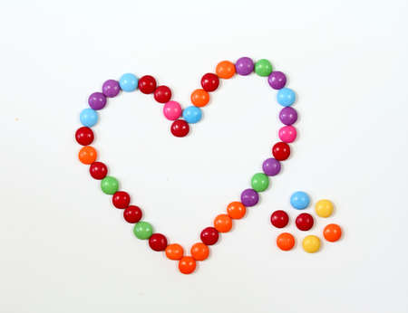 Sweet heart made from colored smarties. Chocolate candies in a shape of heart on white background, flat lay.