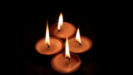 Four butter lamp candles glowing in the dark, mainly used during Diwali or Deepawali festival