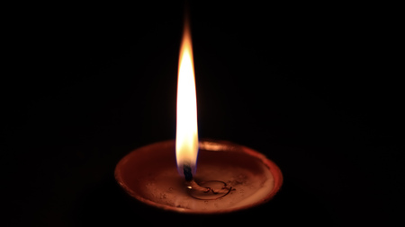 One butter lamp candle glowing in the dark, mainly used during Diwali or Deepawali festival