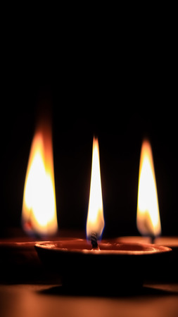Three butter lamp candles glowing in the dark, mainly used during Diwali or Deepawali festival Stock Photo
