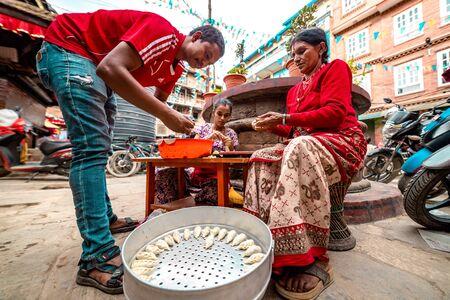 Group of family members preparing momo or dumplings on the side of the road. Street food 에디토리얼