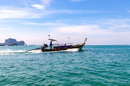 Krabi Town, Thailand - November 23 2019: Tourists sailing in Longtail Boat in Andaman sea off the coast of Thailand.