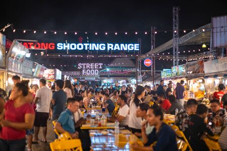Phuket, Thailand - November 26 2019: People enjoying local delicacies at a Night market in Phuket near Patong beach area. Редакционное