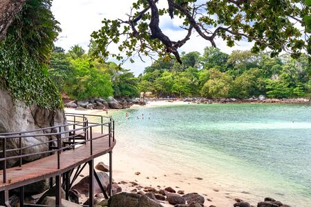 Phuket, Thailand - November 27 2019: Wooden walkway ramp on the shore of Andaman Sea. Famous tourist attraction. Tropical Beach. Perfect summer getaway.