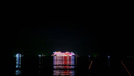 Cruise ship with bright lights sailing in the dark in Andaman sea near Phuket, Thailand. Dinner Cruise Ship