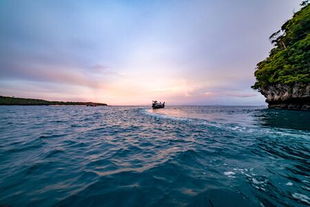 A boat sailing off during golden hour off the coast of Thailand.