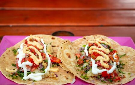 Tacos. Handmade Mexican food served in a pink plate placed on a wooden surface. Authentic Spicy Food.