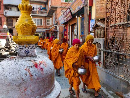 Kathmandu, Nepal - December 17 2019: Young Buddhist monk circulating a Buddhist gompa. Selective Focus - focus on gompa