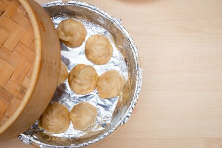 Top view momo or dumplings served in a bamboo steamer placed on a wooden surface.