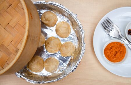 Top view dumplings in a wooden bamboo steamer with homemade delicious sauce
