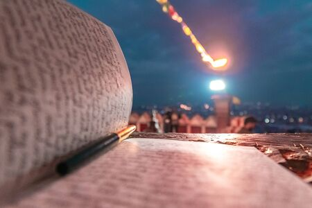 A journal notecopy placed outdoors at an evening against defocused lights of the city. writing blogging student concept. selective focus Stock Photo