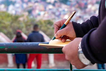 Hand of a young businessman taking notes with a fountain pen on a notecopy.  Student learning online. Blogger. selective focus Stock Photo