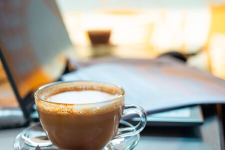 A cup of cappuccino with paperworks resting on a laptop in the backdrop. Working on a project or assignment concept.