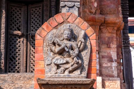 Old ancient stone structures with intricate details of statue of Hindu Gods and Goddesses carved at Swayambhunath Stupa in Kathmandu, Nepal