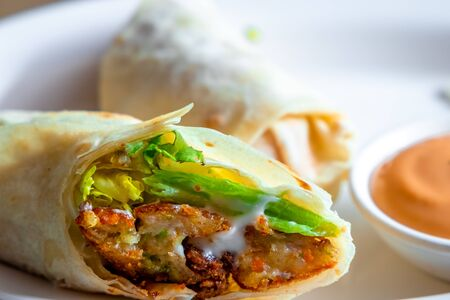 Vegetable Fillings Rolled inside an Indian Bread served on a White Plate with Mayoonaise Sauce