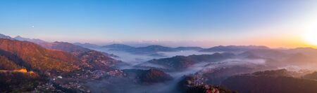 Panorama Moody Dramatic view of mountains covered in fog during sunrise with Great Himalaya Range in the backdrop. Reklamní fotografie
