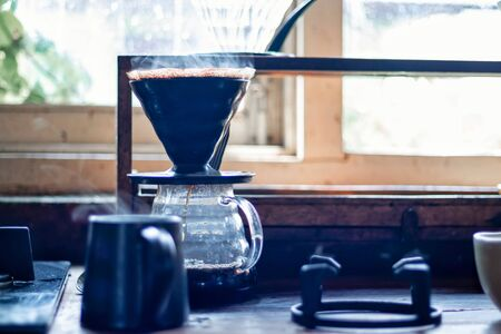 Vapor coming out of a coffee cup and brewing fresh coffee in the background