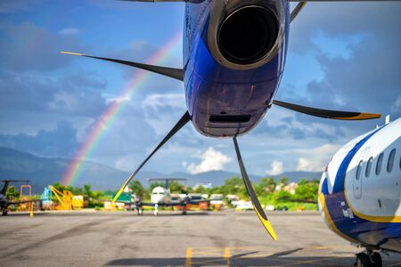 Turboprop engine of an aircraft on tarmac against the rainbow Reklamní fotografie